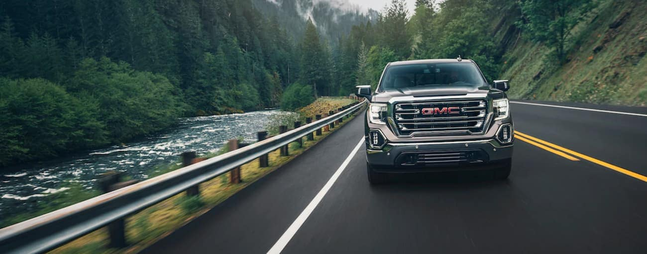 A brown 2019 GMC Sierra driving on a woodland road