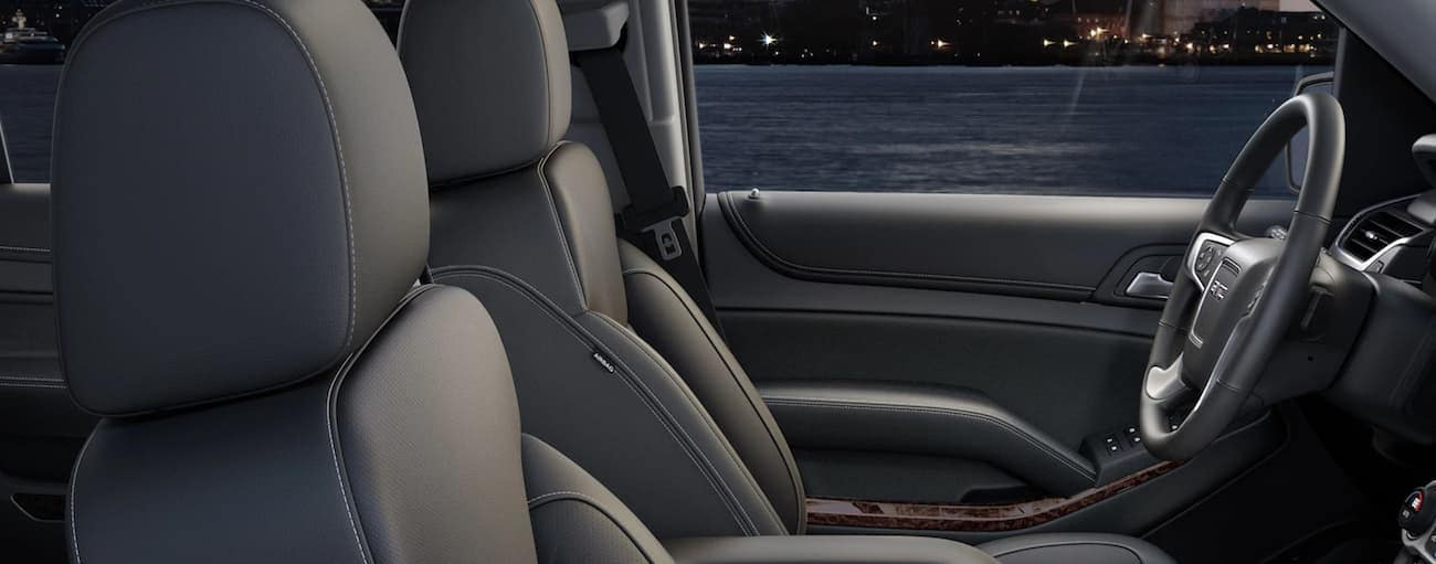 A view of the black leather driver's seat in a 2019 GMC Yukon XL with city in back