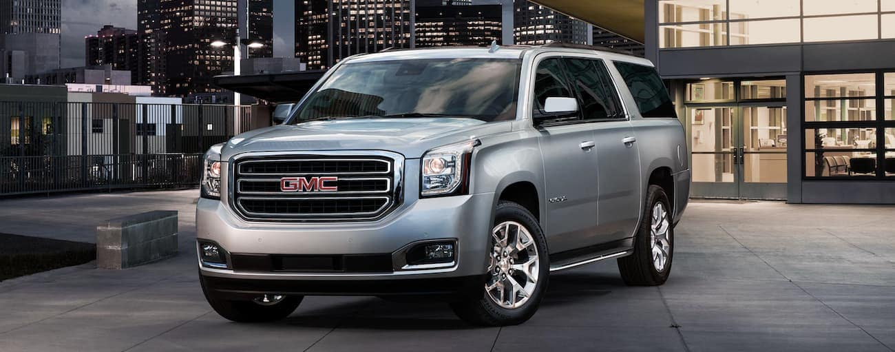 Silver 2019 GMC Yukon XL outside glass building in city at night