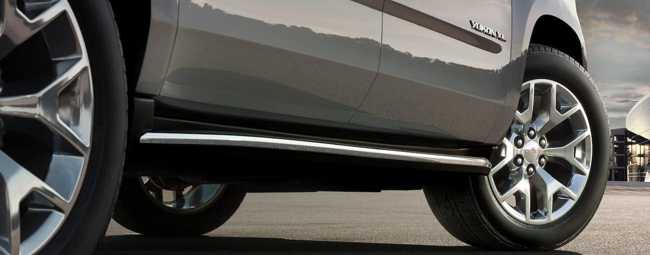 Closeup of wheel and running boards on gray 2019 GMC Yukon XL
