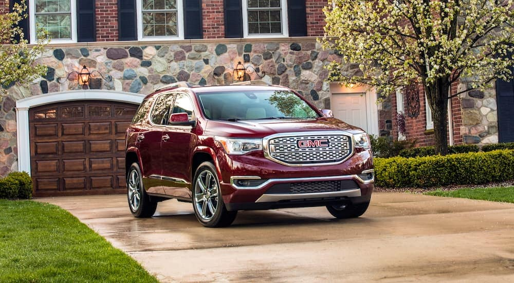 A red 2019 GMC Acadia Denali in front of a house with a stone facade
