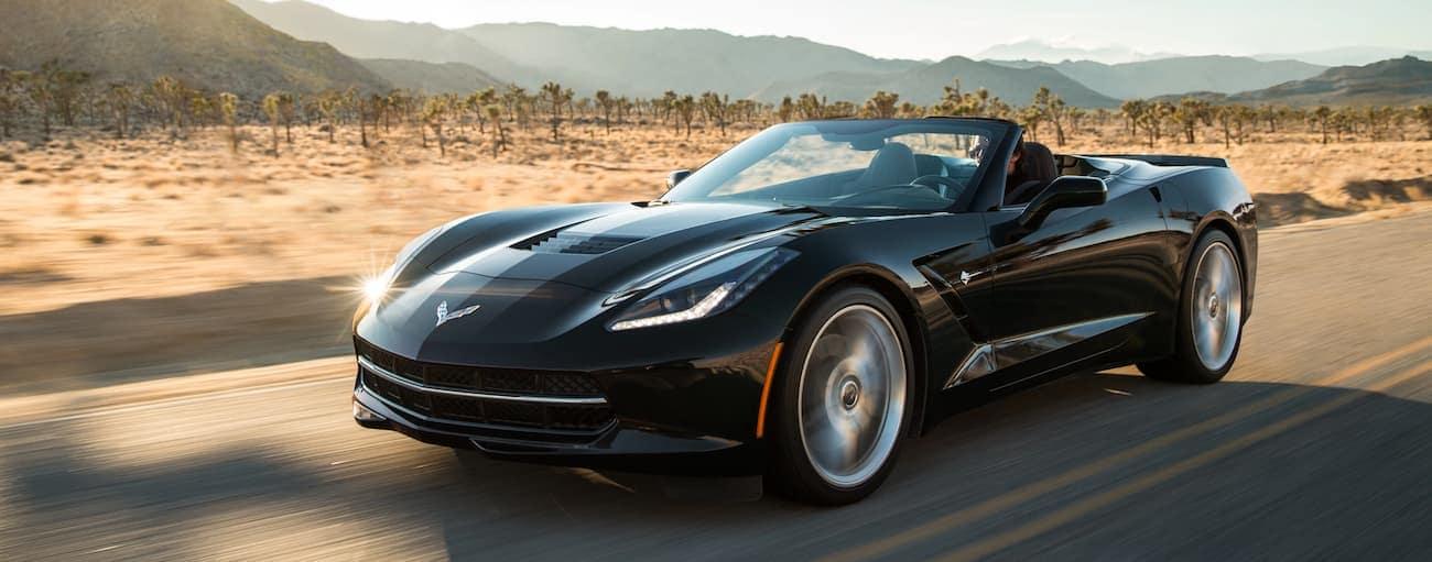 A black convertible 2019 Chevy Corvette Stingray driving in a desert