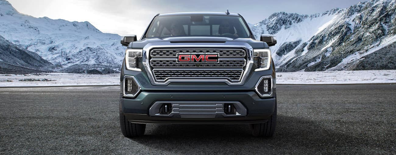 A blue 2019 GMC Sierra Denali with snow covered mountains in back
