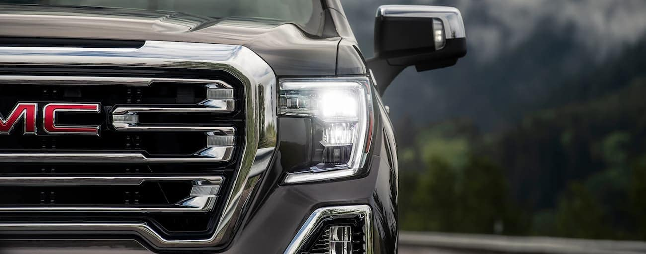 A closeup of a gray 2019 GMC Sierra grille with mountains in back
