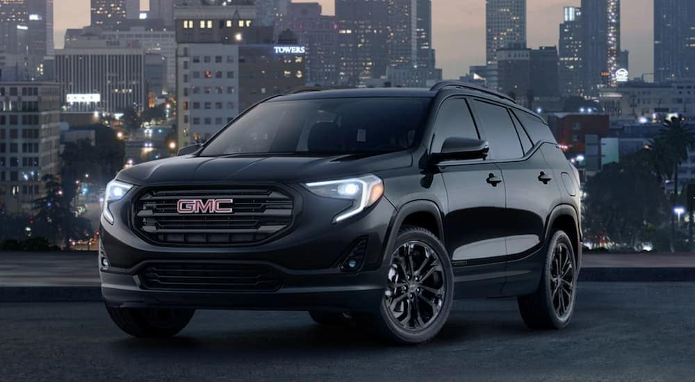 A black 2019 GMC Terrain with a city in the background at night