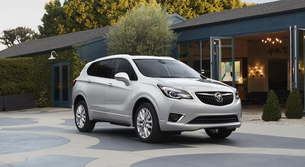A silver 2019 Buick Envision parked outside a local home