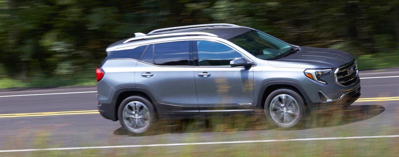 A silver 2019 GMC Terrain driving on a road