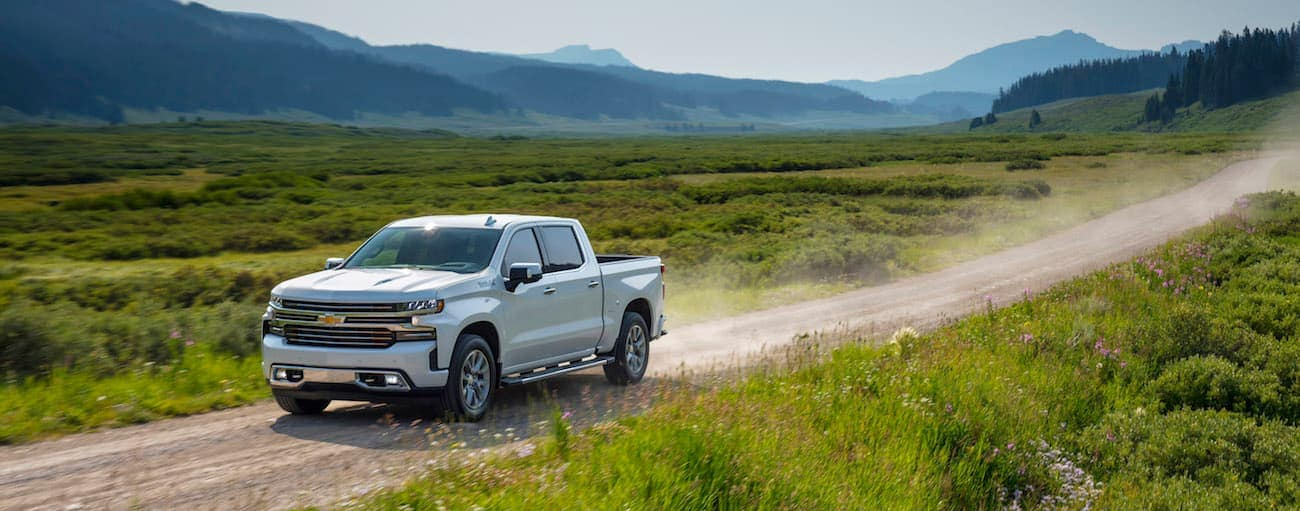 A white Chevy driving through a flower covered valley after winning the 2019 Chevy Silverado vs 2019 Honda Ridgeline