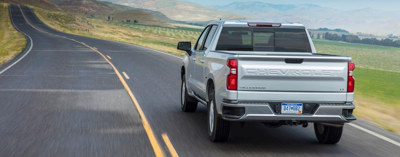 A silver Chevy driving through a valley after winning the battle of 2019 Chevy Silverado vs 2019 Honda Ridgeline