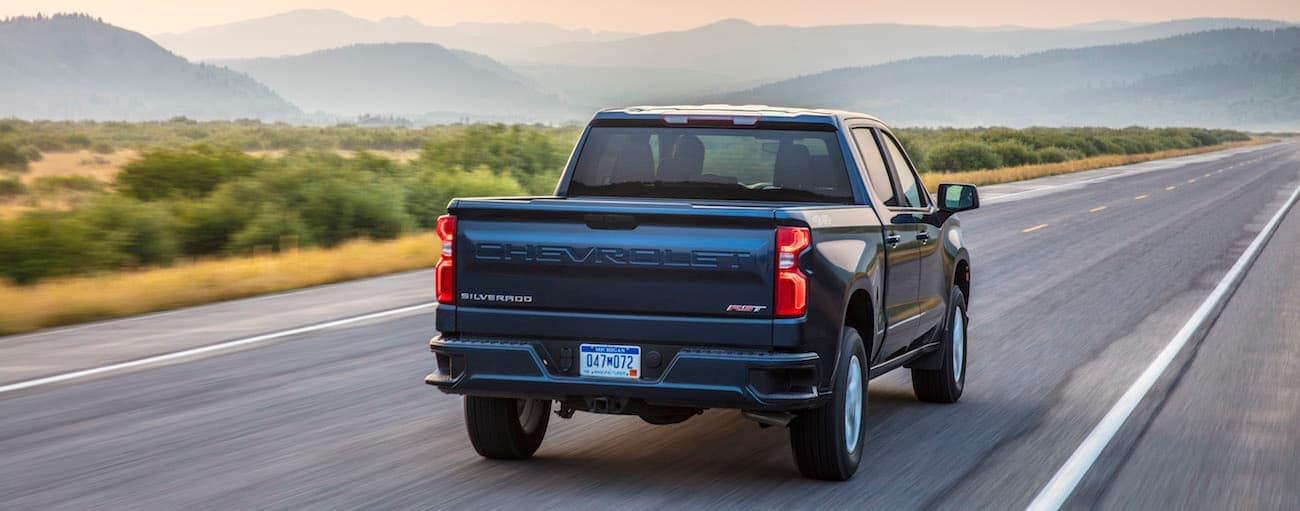 A blue 2019 Chevy Silverado drives off into the sunset with a win in 2019 Chevy Silverado vs 2019 Ford F-150
