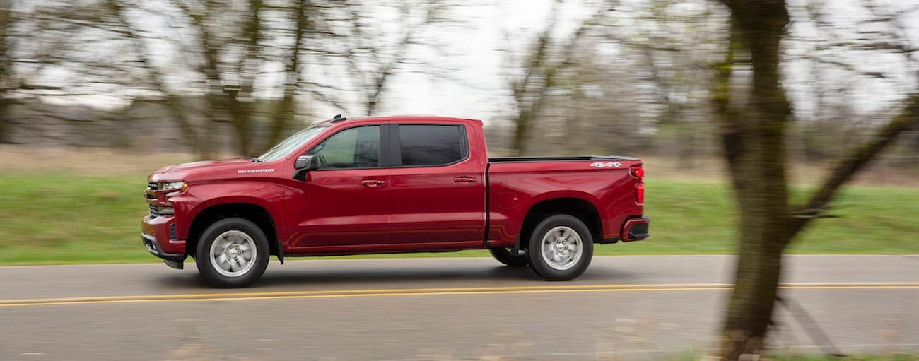 Driving away with the win of 2019 Chevy Silverado vs 2019 Nissan Titan a red Chevy races down a tree-lined road