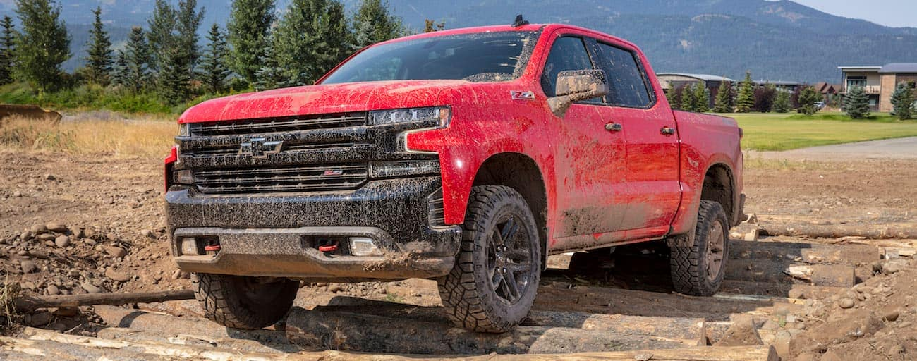 A red Chevy tramples the competition of 2019 Chevy Silverado vs 2019 Ford F-150 while trudging over mud and logs