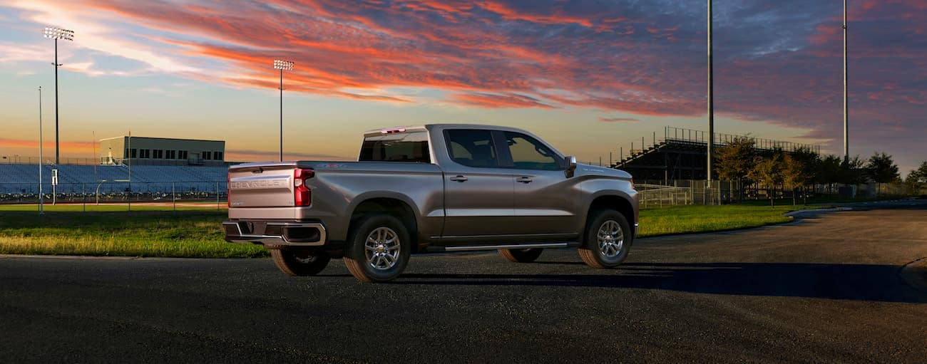 The champion of 2019 Chevy Silverado vs 2019 Nissan Titan. A silver Chevy in front of a football field at sunset
