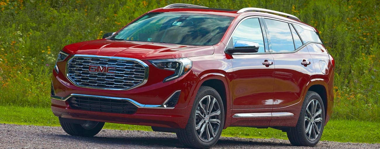 A red 2019 GMC Terrain Denali driving with rolling hills in the back