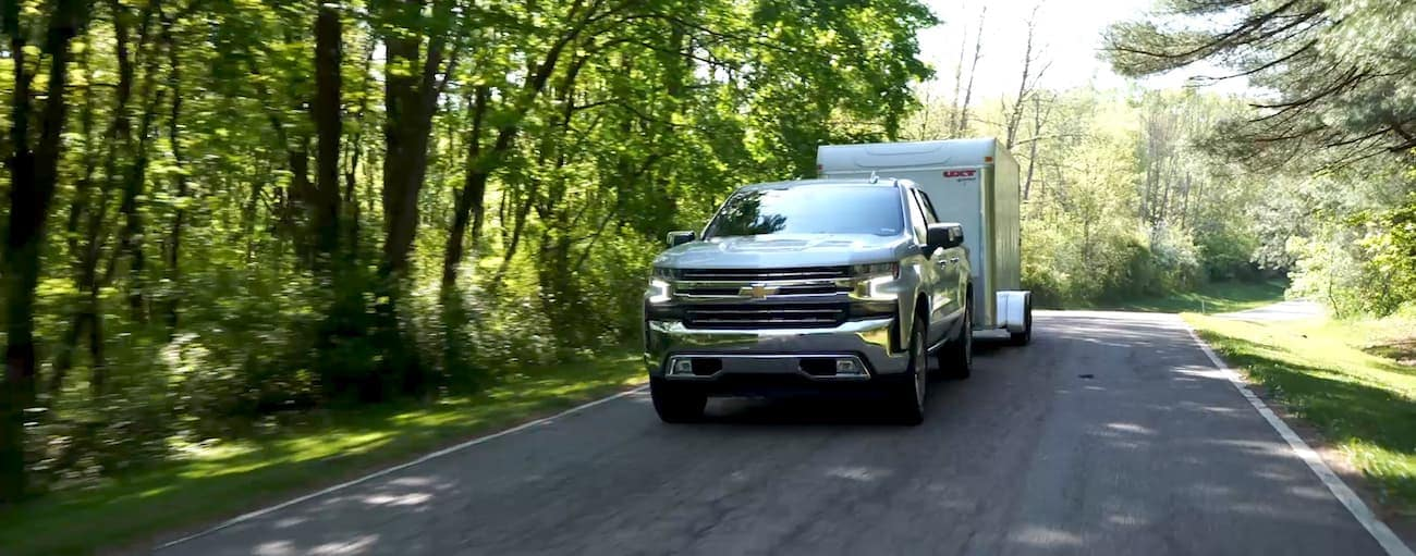 A white Chevy tows a trailer on a wooded street after winning 2019 Chevy Silverado vs 2019 Toyota Tundra