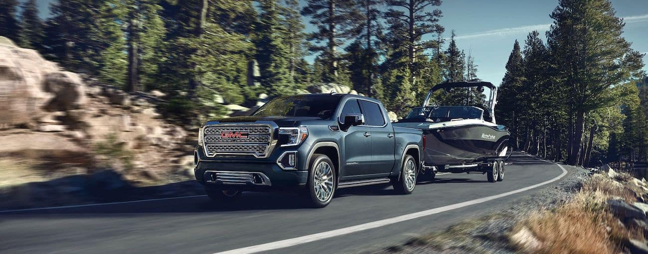 A blue 2019 GMC Sierra 1500 tows a boat up a tree lined mountain road