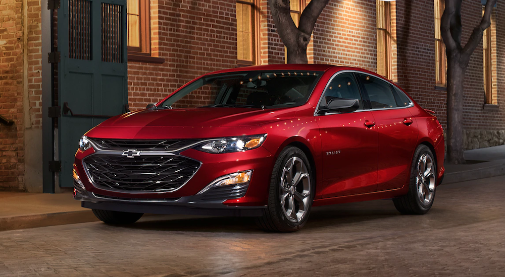 A red 2019 Chevy Malibu is parked in front of a brick building. The lineup of Chevy cars can be seen at your local dealer.