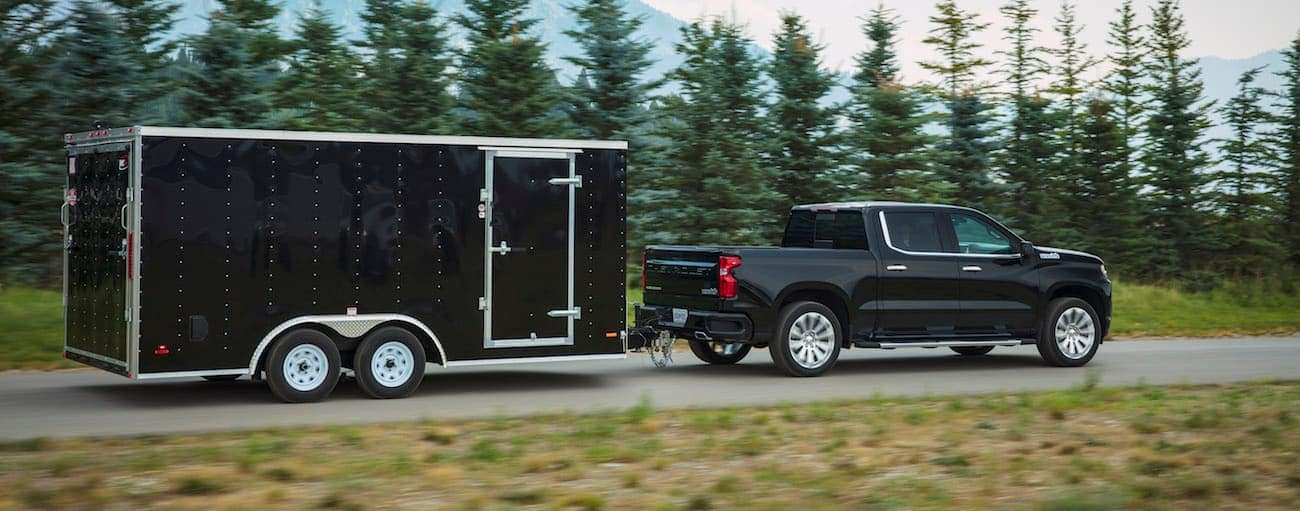A black Chevy tows a trailer while winning the 2019 Chevy Silverado vs 2019 Ram 1500 competition