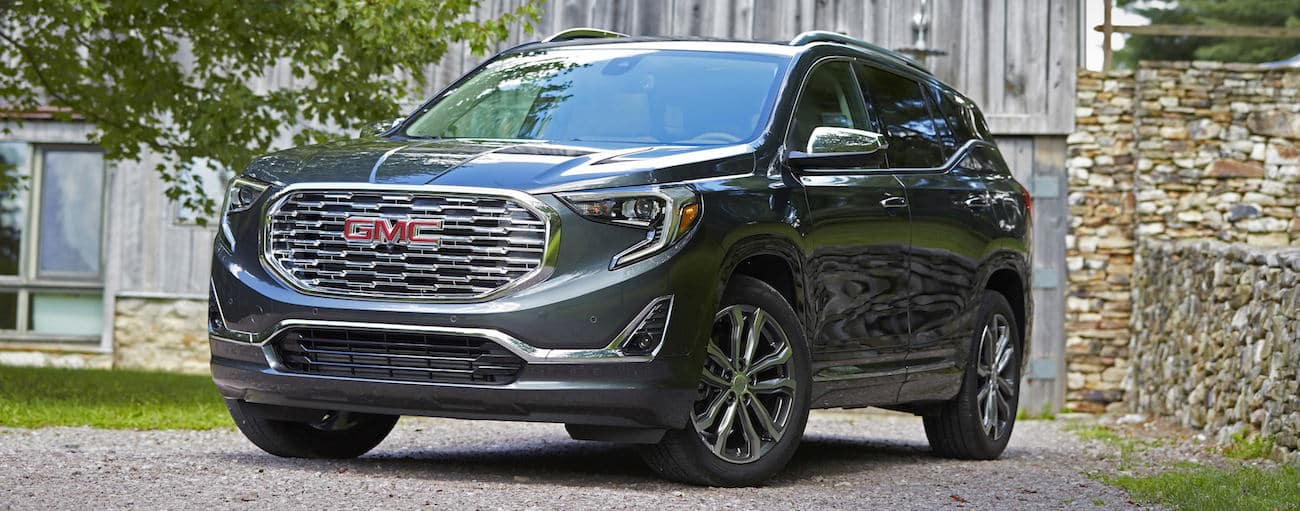 A gray 2019 GMC Terrain Denali in front of a barn and stone wall