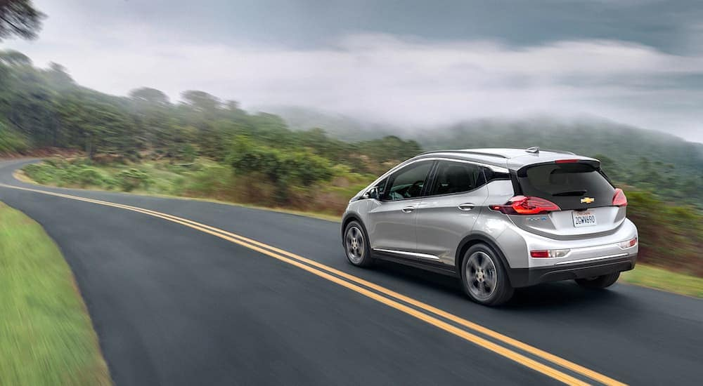 A silver 2019 Chevy Bolt is driving along a high, misty road.