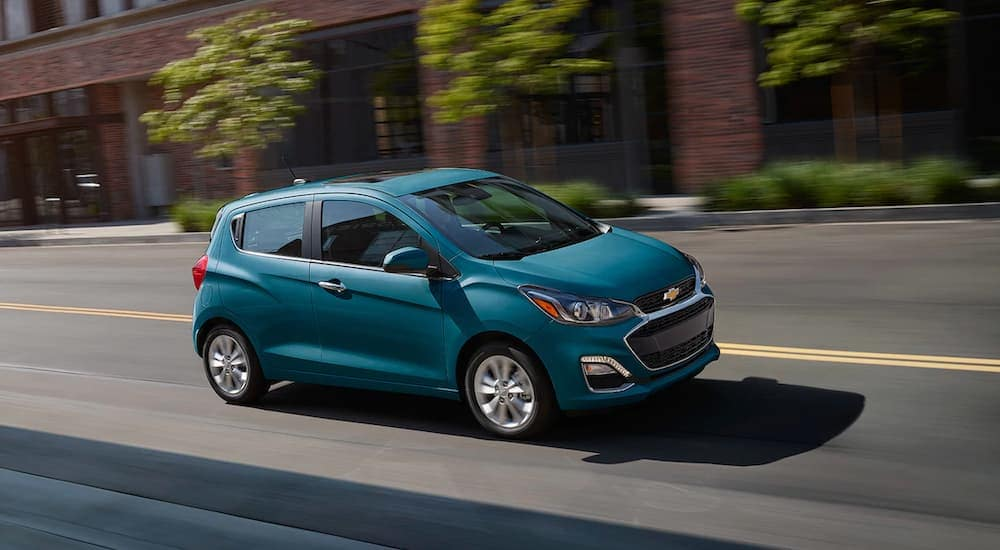 A teal 2019 Chevy Spark is driving in front of a brick building. It is part of the Chevy cars lineup.