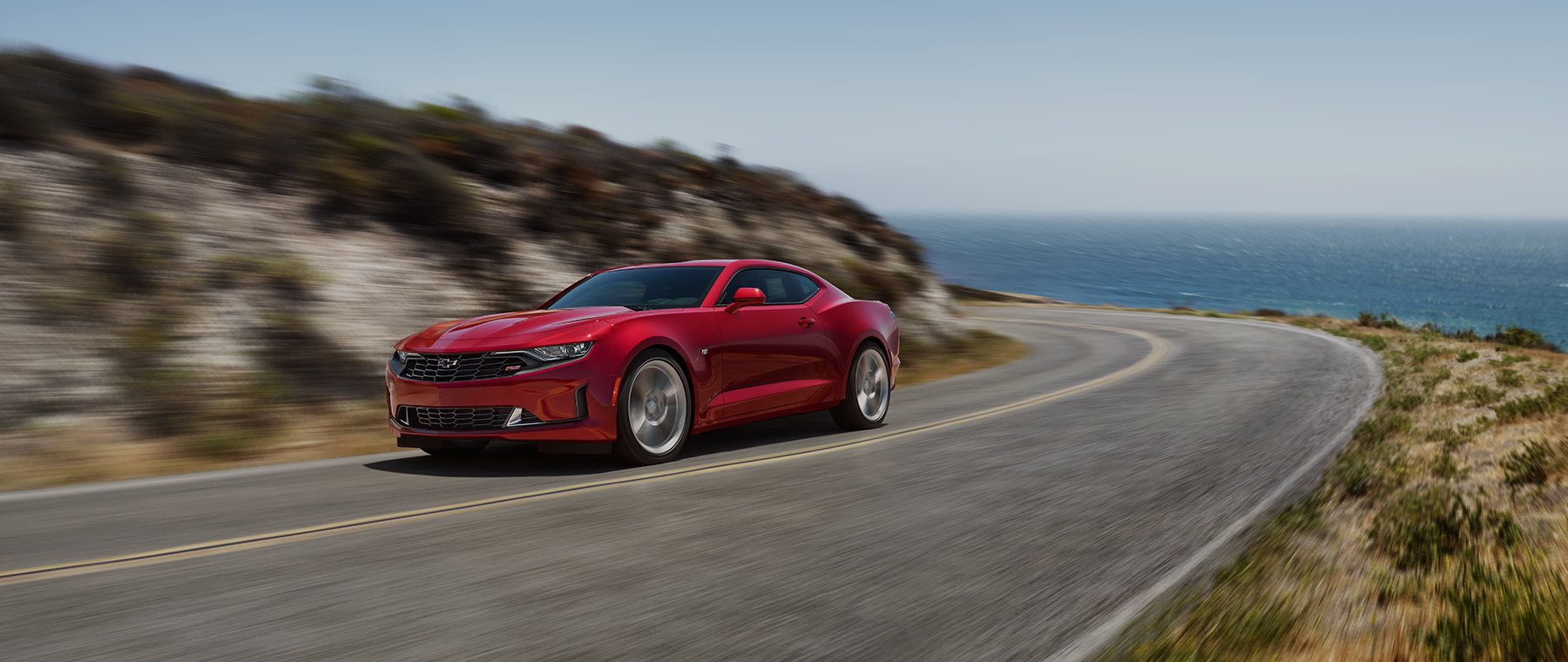 2020 chevrolet camaro red driving down a road