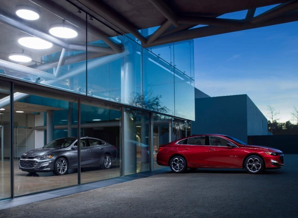 Two, 2019 Chevy Malibu models next to a modern building with glass windows
