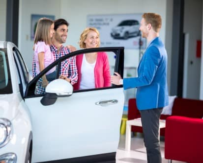 A family standing next to an open car door while talking to a salesman