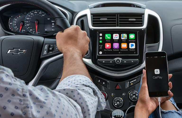 A man pushing buttons on a touchscreen in the 2019 Chevy Sonic