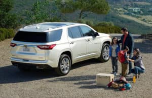 A family with luggage next to the 2020 Chevy Traverse