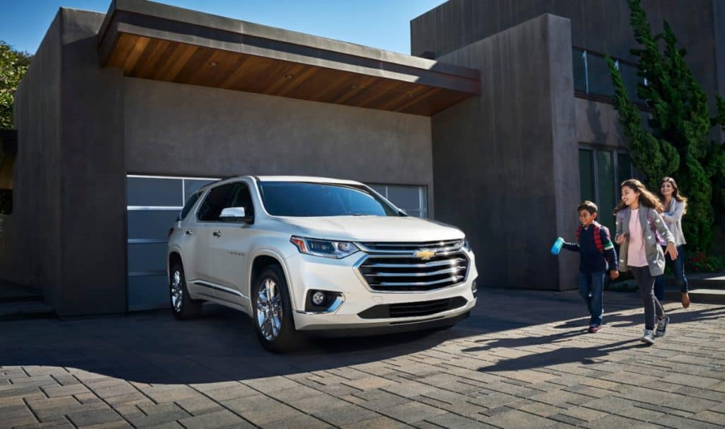A family walking out to the 2019 Chevy Traverse in front of a home