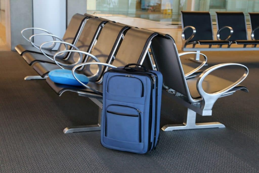 A blue suitcase next to chairs in an airport