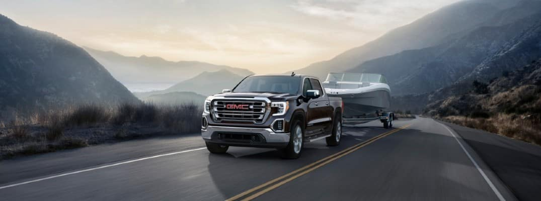 2020 GMC Sierra 1500 driving down the road at sunrise, towing a trailer