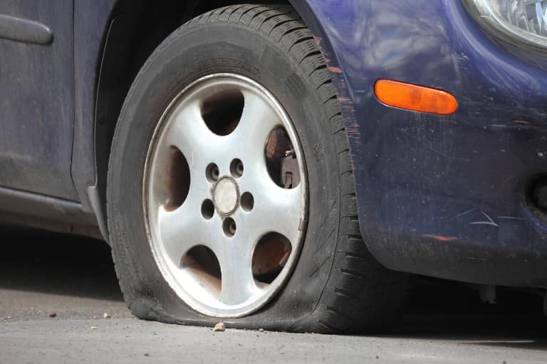 Close-up of a flat tire on a sedan