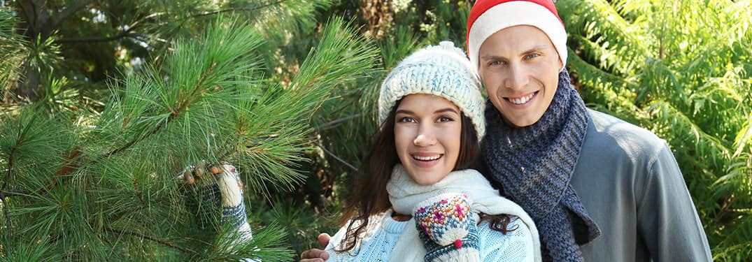 A man and a woman standing next to a pine tree wearing winter hats