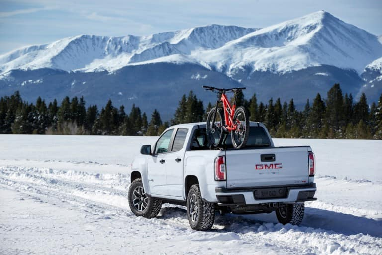 2021 GMC Canyon AT4 driving through snow with bikes in the back