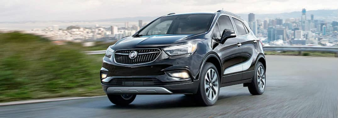 2020 Buick Encore exterior front fascia driver side on road with blurred grass and city