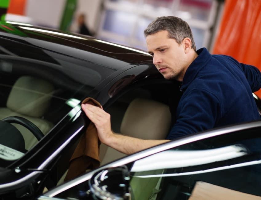 A mechanic polishing the door frame of a car