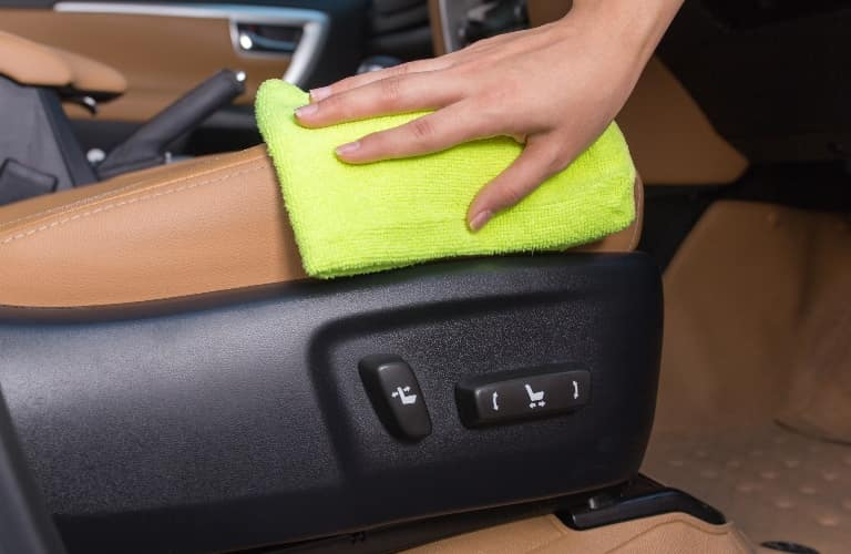 Person washing the side of a seat inside a vehicle