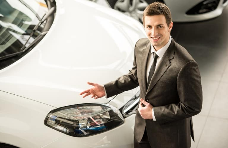 Car salesman standing in front of a car