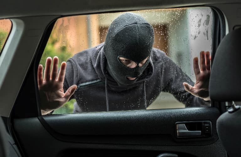 Person looking into the window of a vehicle