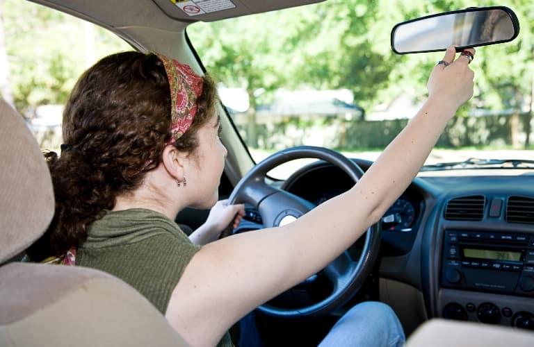 Teenage driver adjusting her mirror