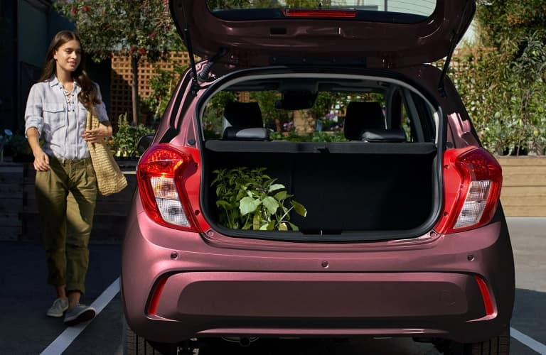 Woman walking up to the back end of the 2021 Chevrolet Spark