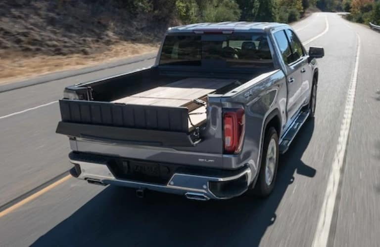2021 GMC Sierra 1500 driving away with items in the bed of the truck