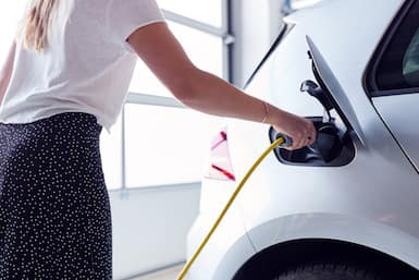 woman charging electric vehicle at home