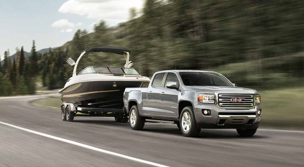 Silver 2019 GMC Canyon towing boat on woodland road