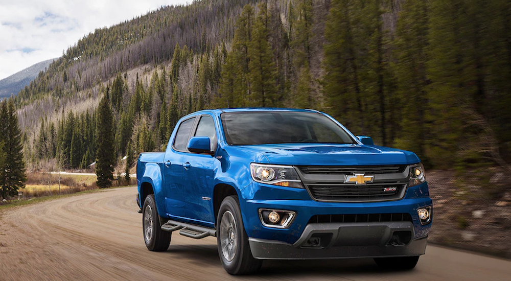 Blue 2018 Chevy Colorado drives down a dirt mountain road