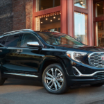 A black 2019 GMC Terrain exists a trendy restaurant parking lot