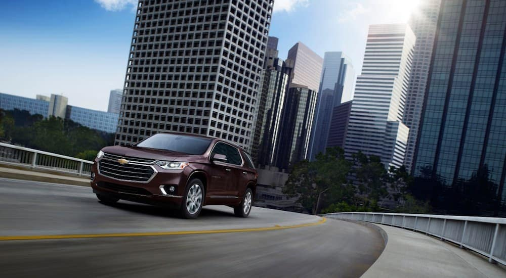 Maroon 2019 Chevy Traverse driving in city