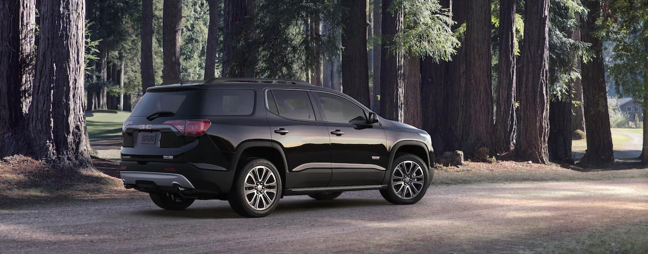 A black 2019 GMC Acadia All Terrain in the woods